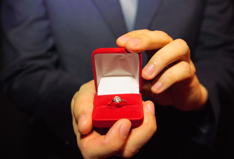 Man in a blue suit gives a ring with a diamond in a red box