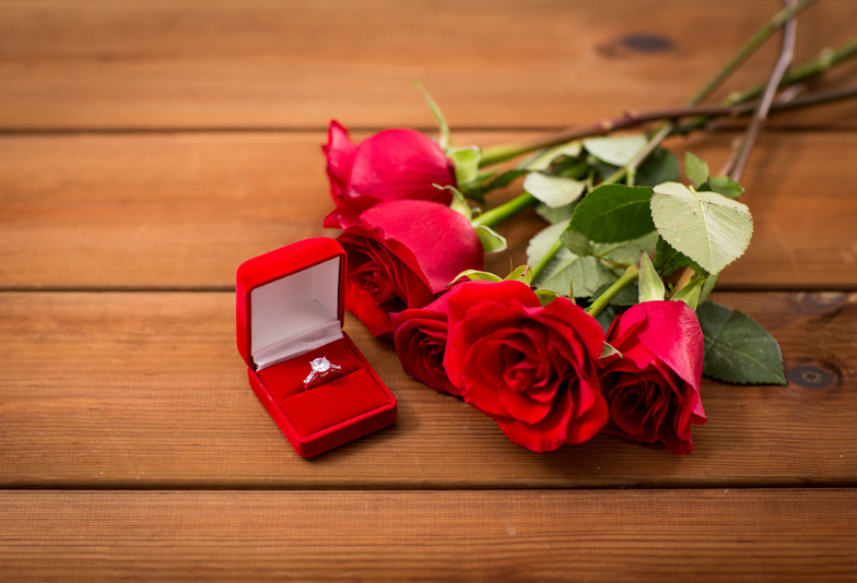 love, proposal, valentines day and holidays concept - close up of gift box with diamond engagement ring and red roses on wood