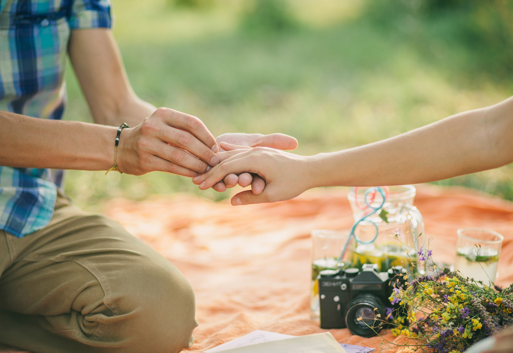 engagement ring proposal hands close up in picnic