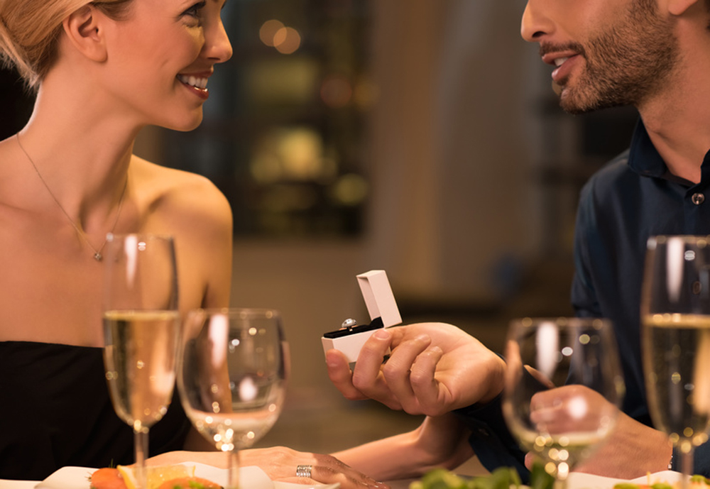 Smiling man proposing his girlfriend at restaurant. Man holding box with solitaire ring making marriage propose to his girlfriend. Young handsome husband gifting a ring to wife on anniversary. Man asking marry to his happy girlfriend