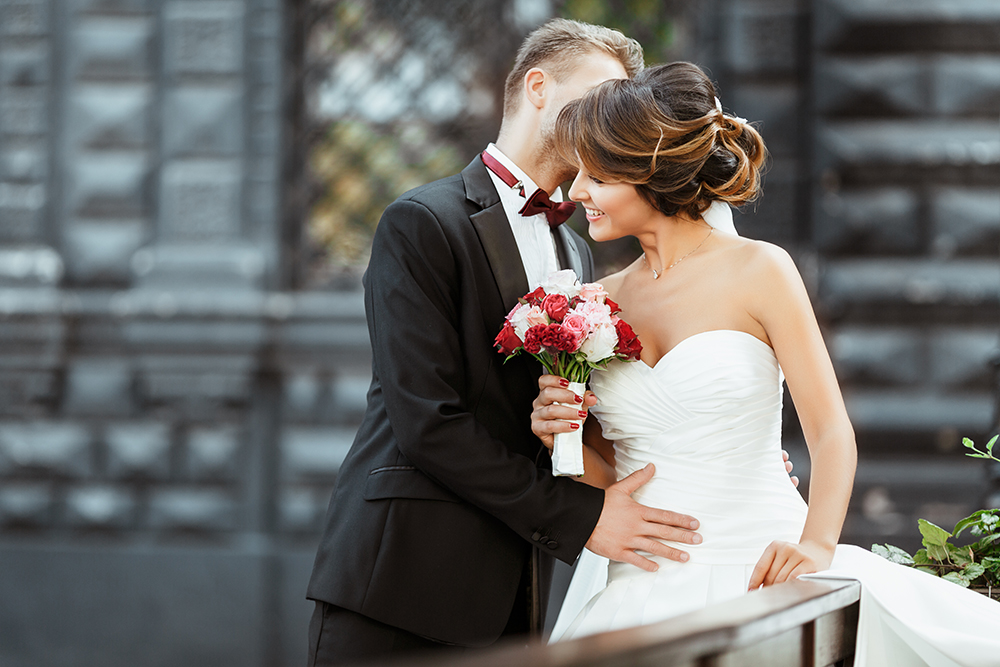 Wedding photo shooting. Bride and bridegroom standing with bouquet and embracing. Woman wearing white dress and veil and man wearing suit. Outdoor, waist up, profile