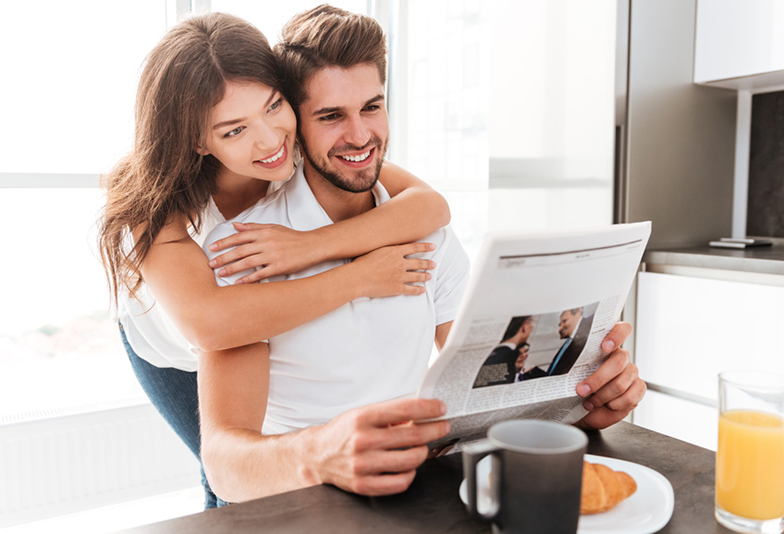 Happy young couple hugging and reading newspaper on the kitchen
