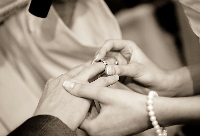 結婚指輪を着けるカップル